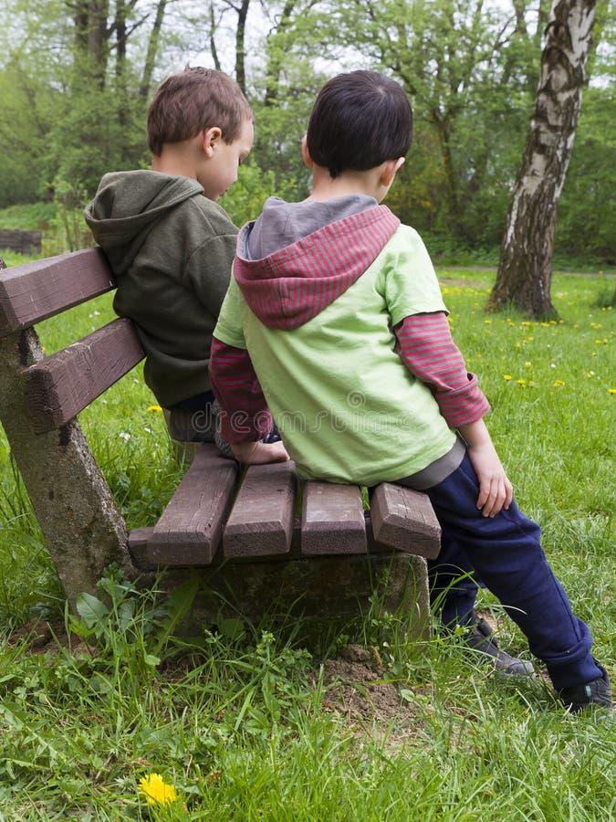 Barn på bänk parkerar in royaltyfri fotografi