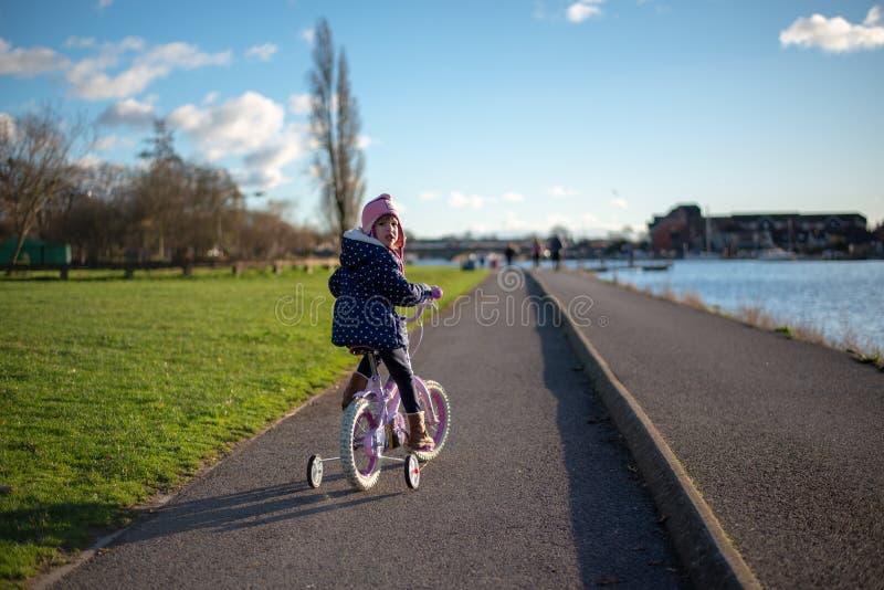 Barn på cykeln på banan vid floden royaltyfria bilder
