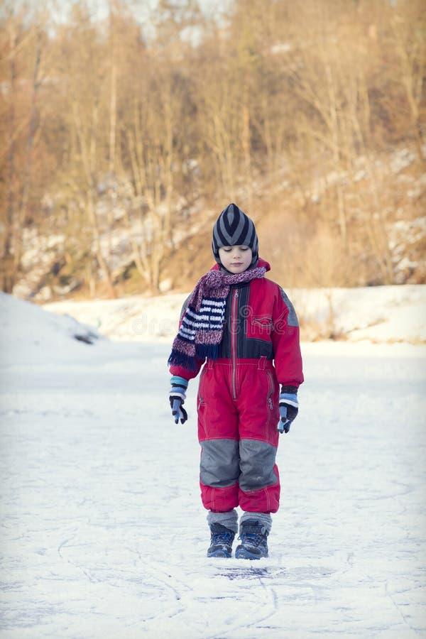 Barn på den djupfrysta floden i vinter royaltyfria bilder