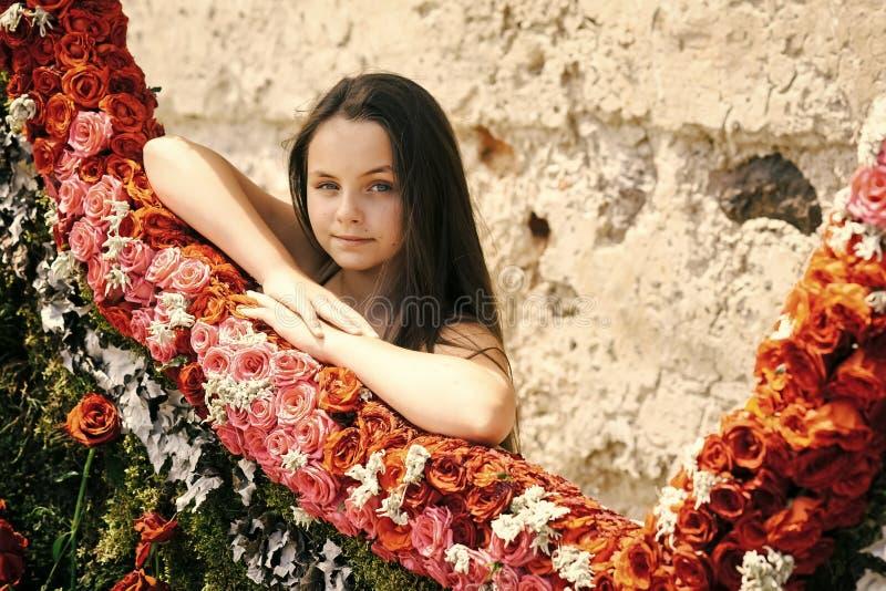 Barn på en blommamässa Liten förtjusande flickaställning nära färgrika blommor i vårträdgård royaltyfri fotografi