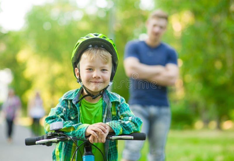 Barn på en cykel med fadern i parkera royaltyfri fotografi