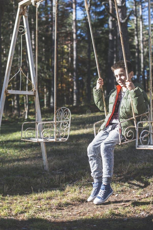 Barn på en swing royaltyfri fotografi