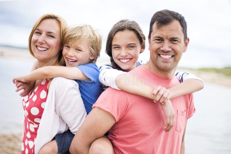 Barn på föräldrar tillbaka på stranden arkivfoton