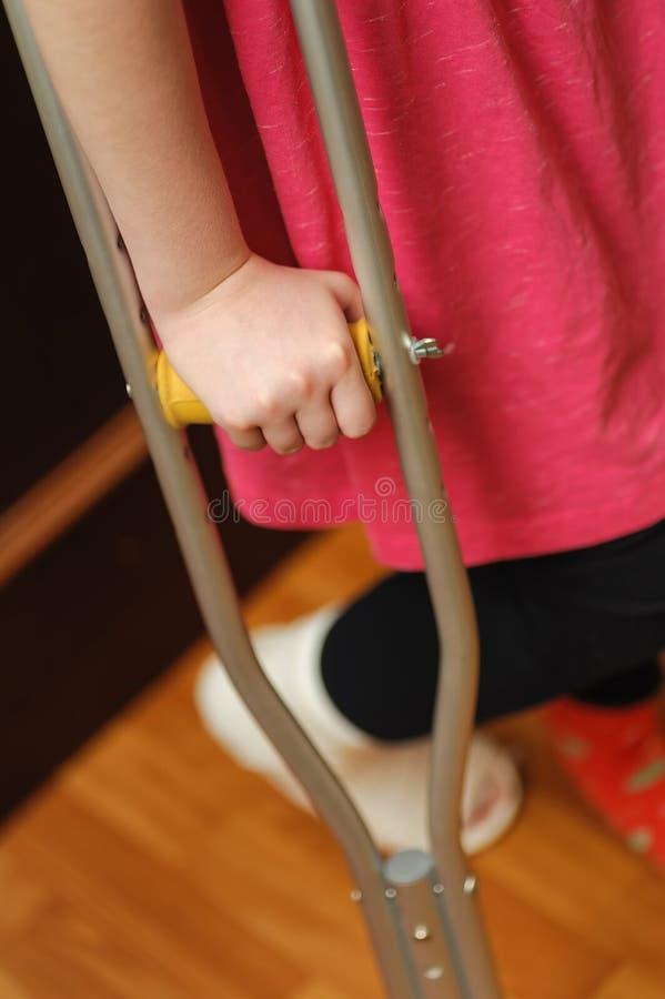 Barn på kryckor med benet i gips arkivfoton