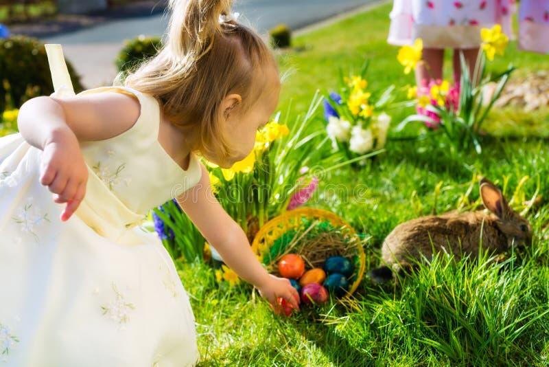 Barn på påskägget jagar med kaninen royaltyfria bilder