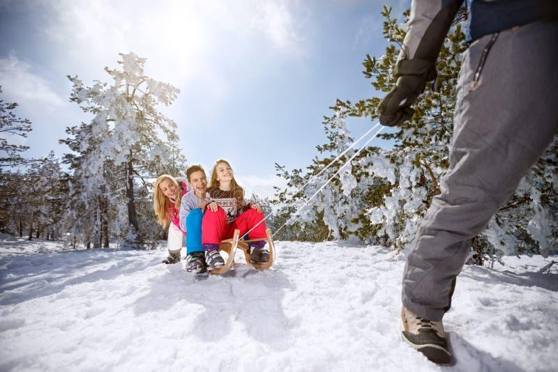 Barn på pulkan som tycker om på vinterferie arkivfoton