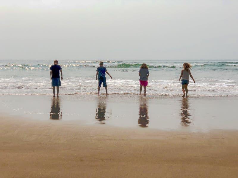 Barn på stranden med reflexioner i våt sand royaltyfria bilder