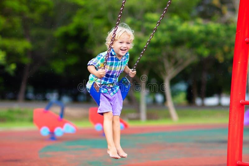 Barn p? lekplats gungaungar spelar utomhus- royaltyfri fotografi