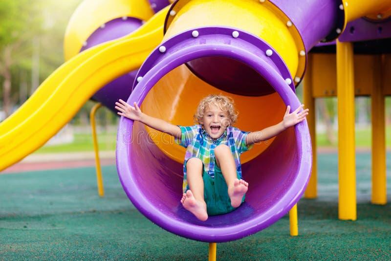 Barn p? lekplats Ungar spelar utomhus- royaltyfri foto
