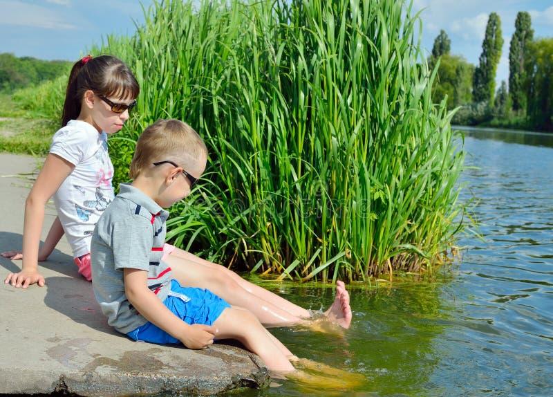 Barn plaskar deras fot i vattnet av sjön arkivbild