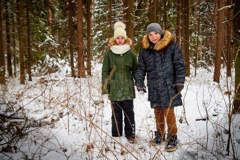 Barn pojke och flicka som går i snöskog i en vinterdag Tonåringar som har tur och att vila i den utomhus- helgen royaltyfri bild
