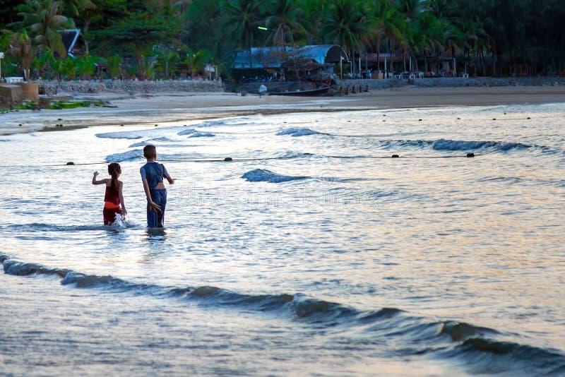 Barn, pojke och flicka som spelar i vågor på den sandiga stranden av den tropiska ön barn för kvinna för fritidbergsommar arkivfoto