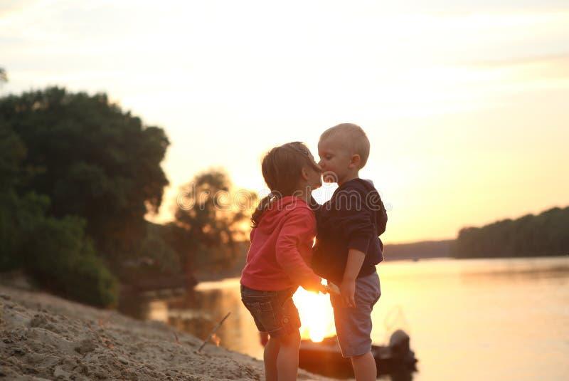 Barn pojke och flod för flickakysssolnedgång arkivfoto