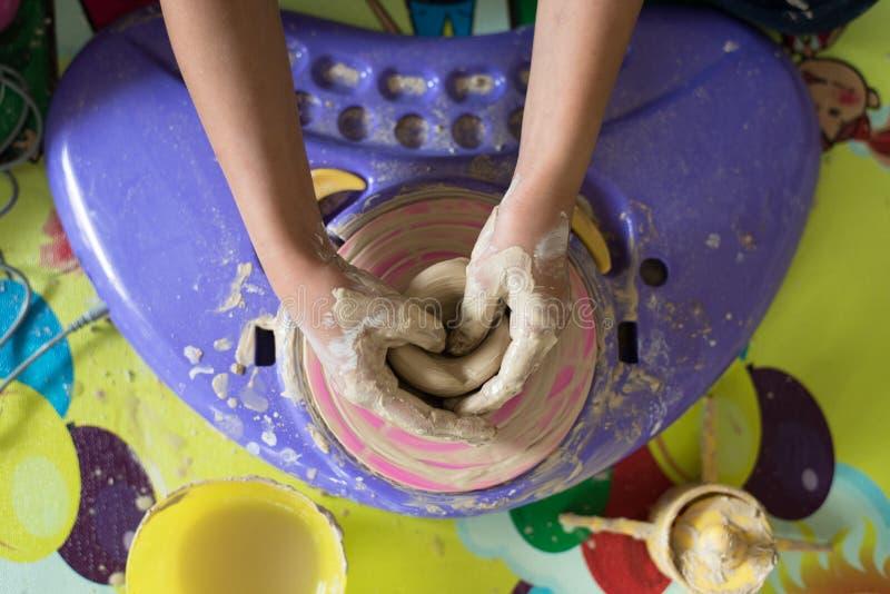 Barn räcker att spela med lera som gör krukmakeri fotografering för bildbyråer