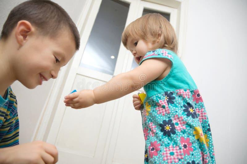 barn returnerar att leka familjögonblick i äkthet Liten flicka med brodern syskon Autentisk livsstil arkivbild