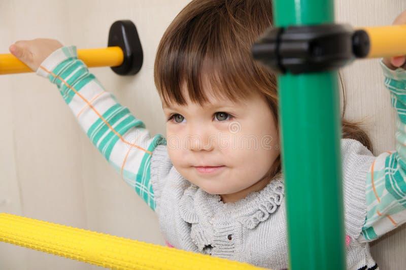Barn returnerar genomkörare Liten flicka på gymnastisk stång Barnhälsovård och gymnastikbegrepp Lycklig och sund barndom royaltyfri fotografi