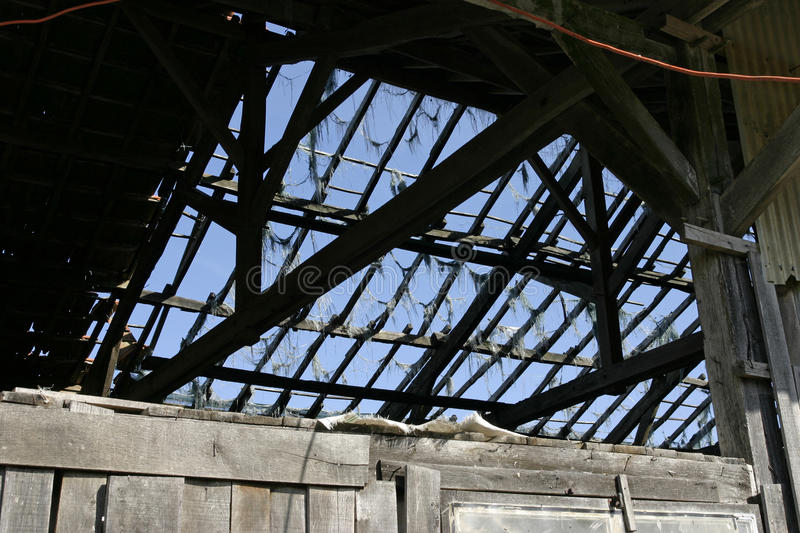 Barn roof with no slates and open. Wooden barn roof with no slates and open. In need of repair. Derelict roof stock image