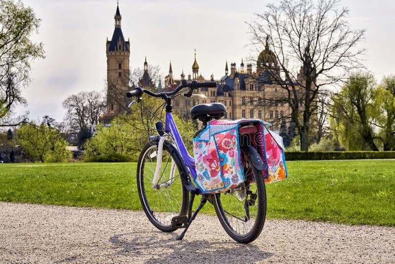 Barn 's cykel med sadelväskor i parken, med Schwerin Castle i bakgrunden royaltyfria bilder