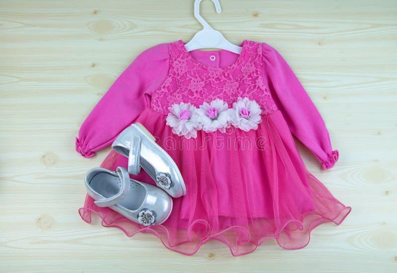 Barn` s som beklär eleganta festliga rosa färger, klär med skor royaltyfria foton