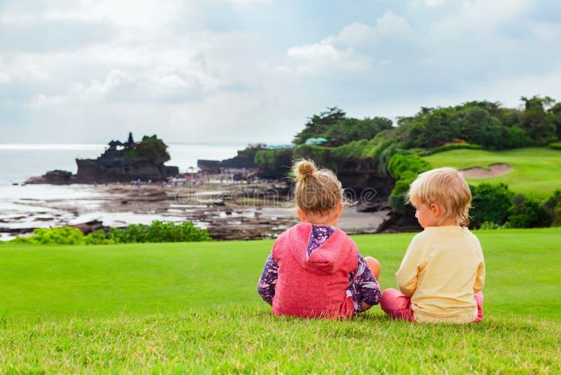 Barn ser från den höga klippan på den BalinesetempelTanah lotten arkivfoton