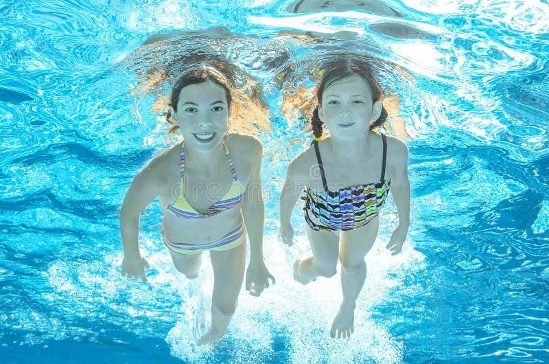Barn simmar i den undervattens- pölen, flickor har gyckel i vatten royaltyfri fotografi