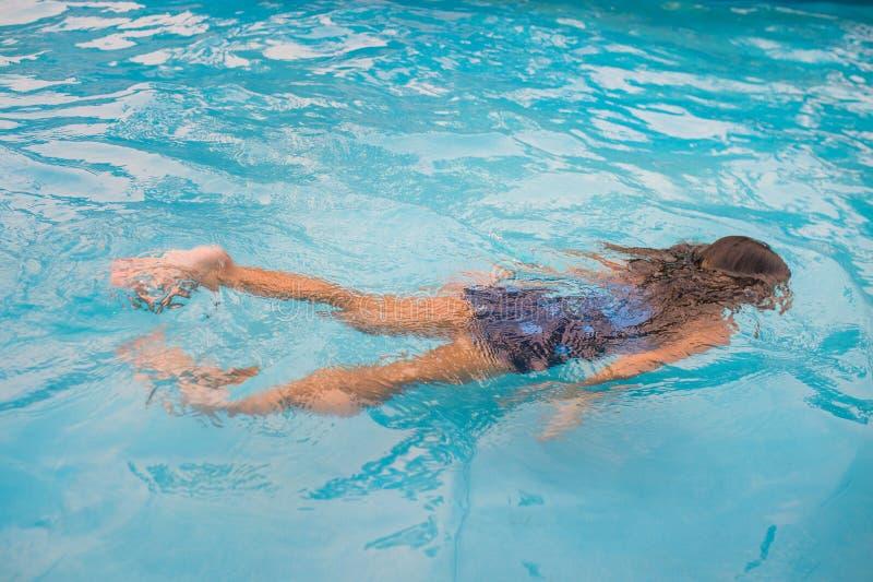 Barn simmar i den undervattens- pölen, lyckliga aktiva flickor har gyckel i vatten arkivbilder