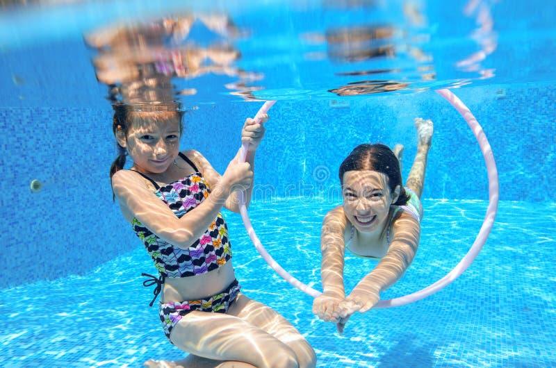 Barn simmar i den undervattens- pölen, lyckliga aktiva flickor har gyckel under vatten, ungesport fotografering för bildbyråer