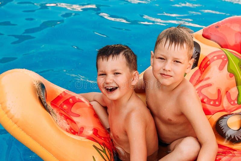 Barn simmar i pölen på en uppblåsbar madrass arkivbild
