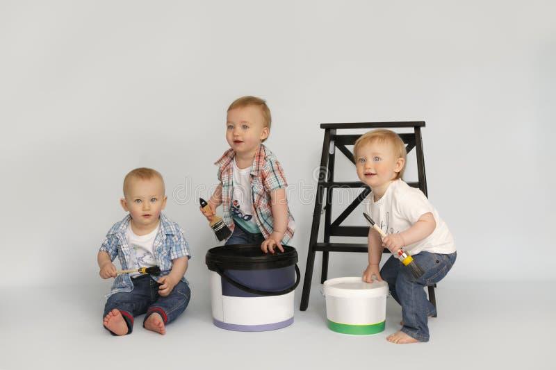 Barn sitter bredvid banker målar i målarfärg för handhållborste stroymatkrialy arkivfoton
