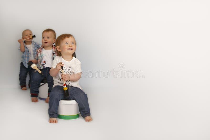 Barn sitter på stora cans av målarfärg royaltyfria foton
