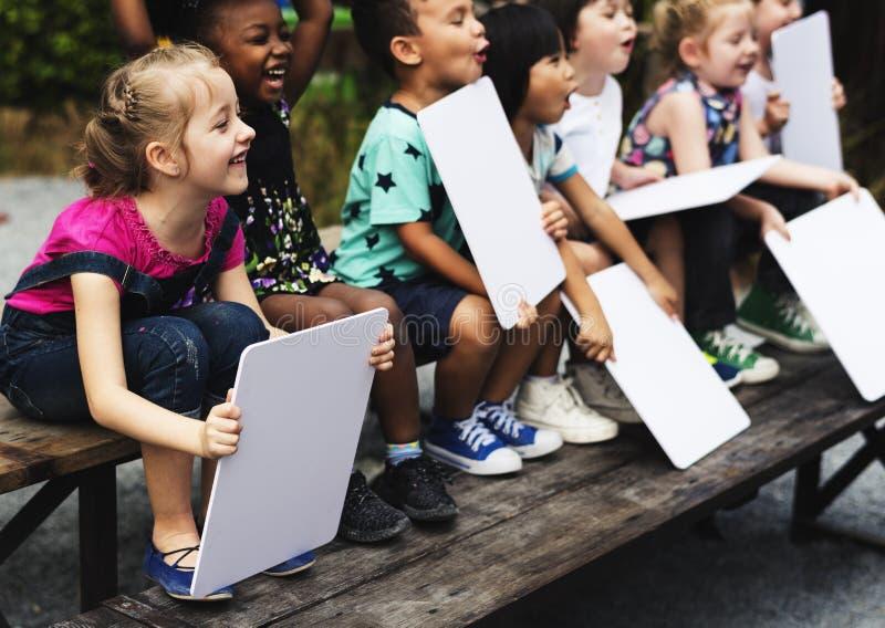 Barn sitter rymma tillsammans plakatet royaltyfri fotografi