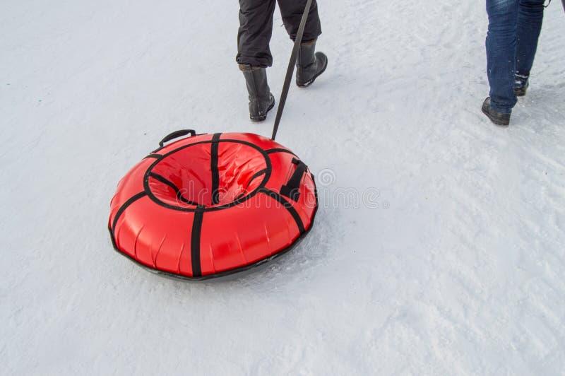 Barn släpade släderör för att rida en berg-och dalbana i stad parkerar i vinter arkivbilder