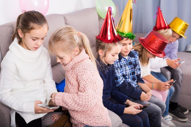 Barn som är lyckliga att spela med mobiltelefoner tillsammans på matställen royaltyfria foton