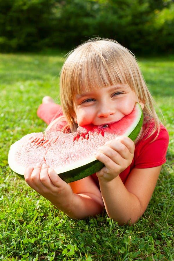 Barn som äter den utomhus- melon royaltyfri bild