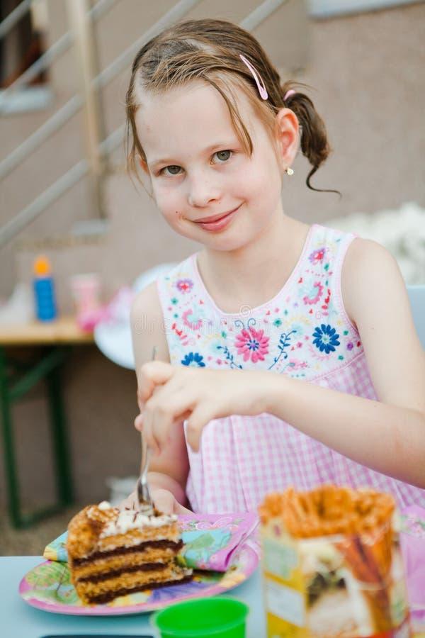 Barn som äter födelsedagkakan - naturlig verklig bakgrund arkivbild