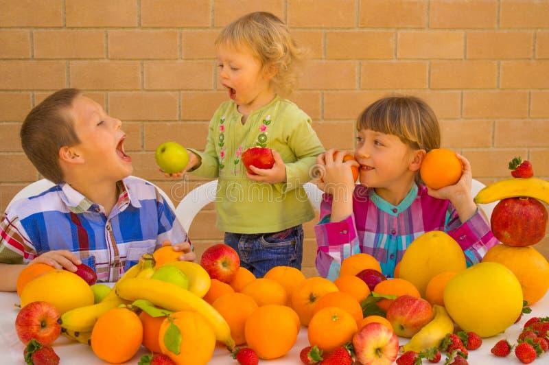 Barn som äter frukter royaltyfri bild