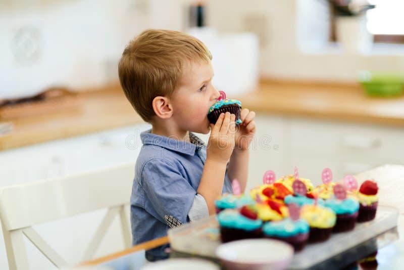 Barn som äter härliga muffin arkivfoto