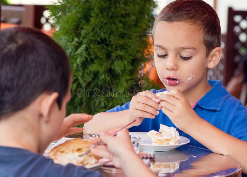 Barn som äter kakan i kafé arkivbild