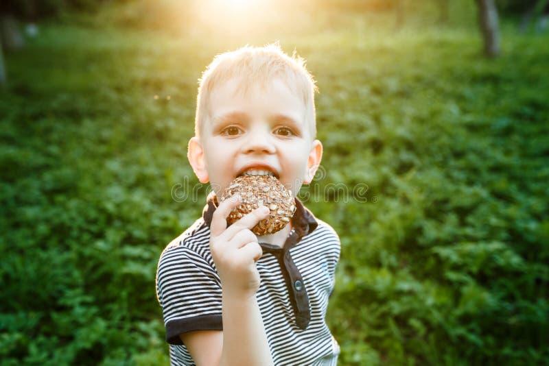 Barn som äter kakan på naturbakgrunden royaltyfria foton