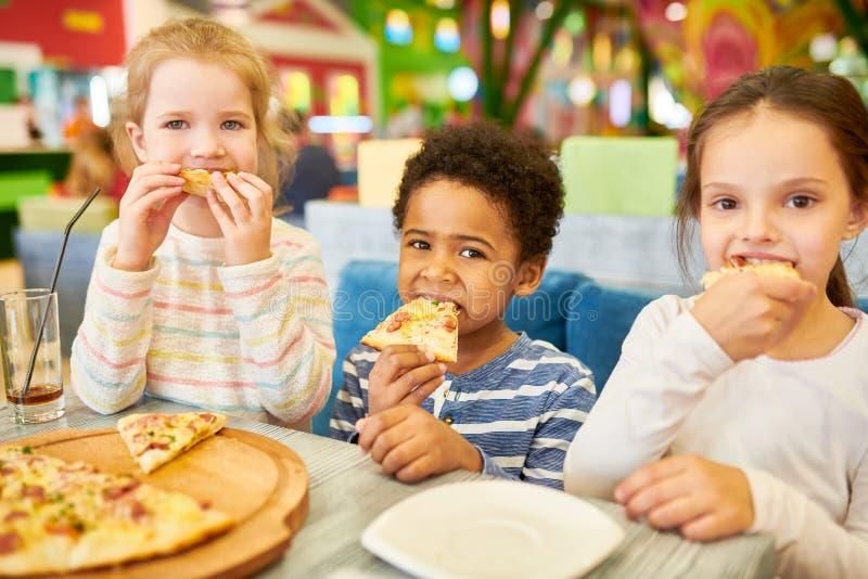 Barn som äter pizza i kafé arkivfoton