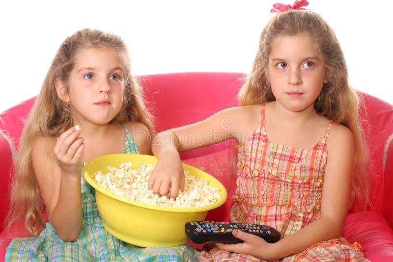barn som äter popcornwatchi royaltyfria bilder