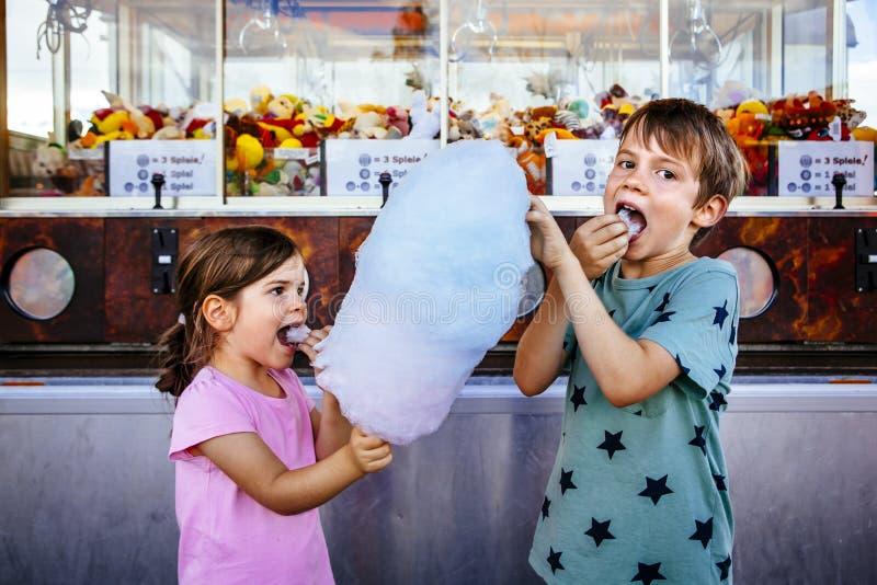 Barn som äter sockervadden på karnevalet arkivfoton