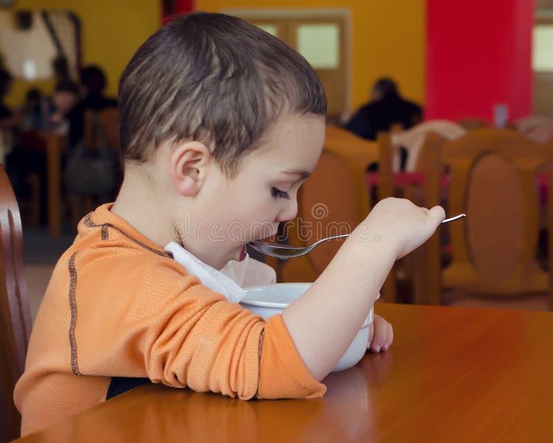 Barn som äter soppa i restaurang royaltyfri bild