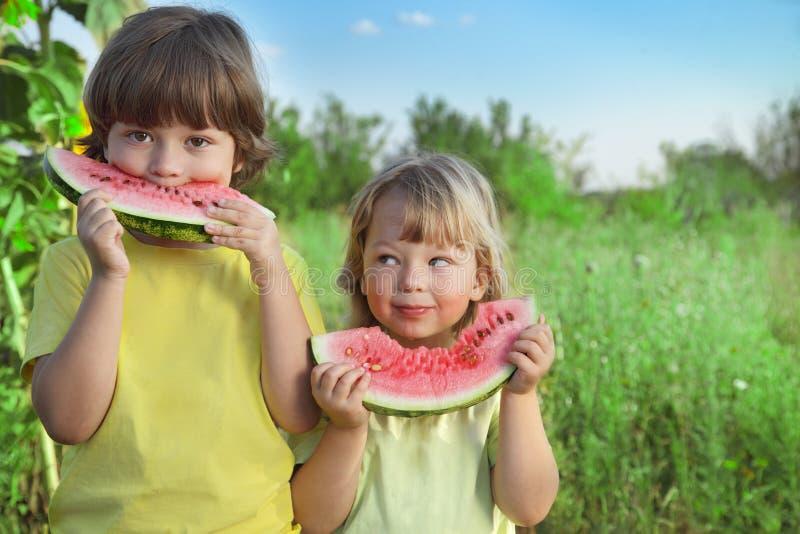 barn som äter vattenmelon i trädgården royaltyfri foto