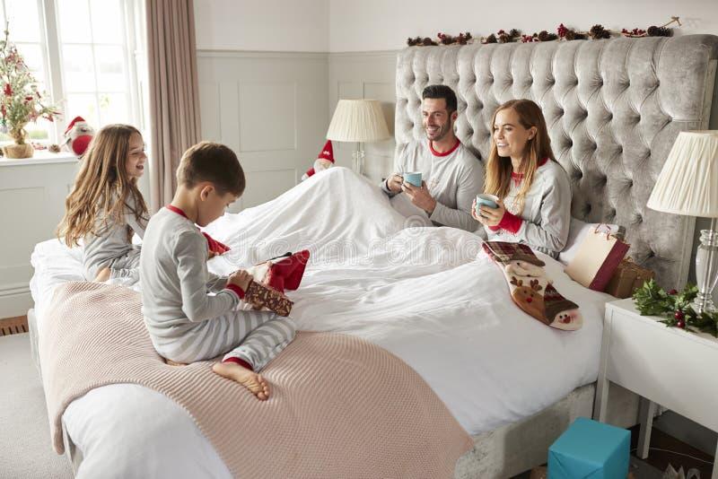 Barn som öppnar gåvor från föräldrar som dem Sit On Bed Exchanging Present på juldagen arkivbild