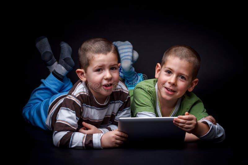 Barn som använder den elektroniska minnestavlan royaltyfri fotografi
