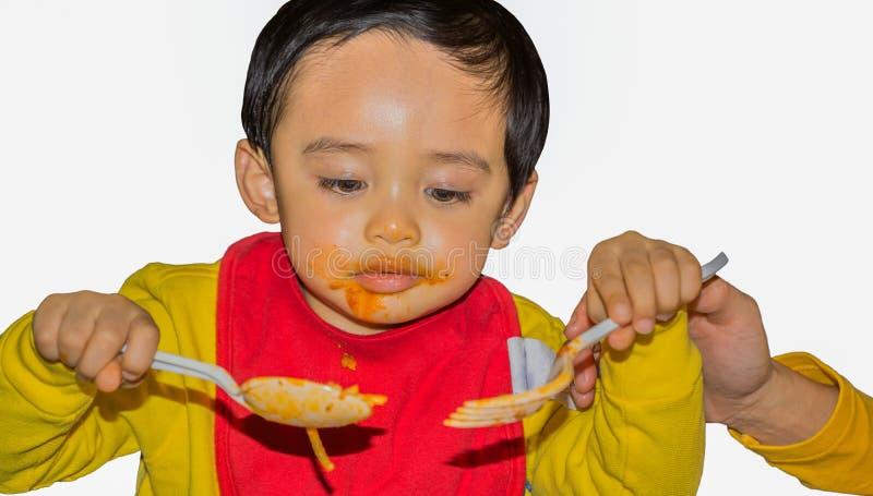 Barn som använder den plast- skeden och gaffeln royaltyfri fotografi