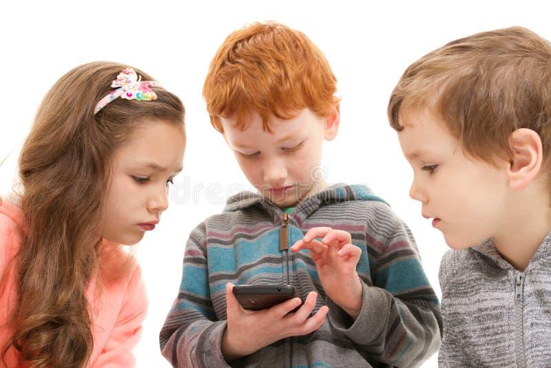Barn som använder ungesmartphonen arkivfoto