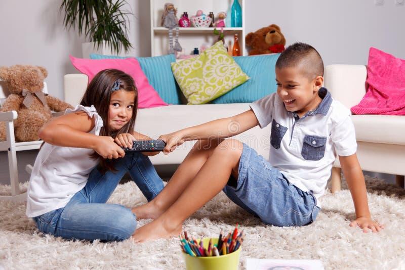 Barn som argumenterar om hållande ögonen på TV royaltyfri fotografi