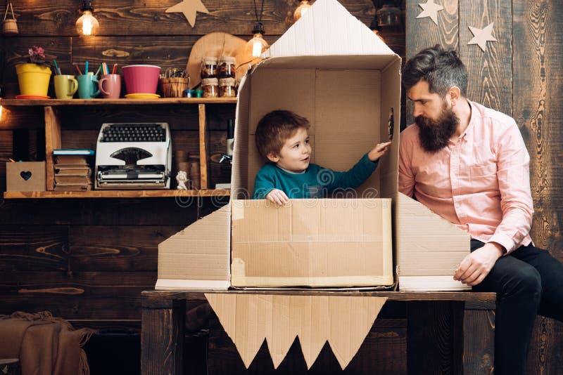 Barn som astronaut med leksakraket som spelar och drömmer av att bli astronaut Stående av den roliga ungen och fadern familj royaltyfri foto